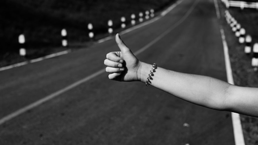 A hitchhiker with her thumb out.