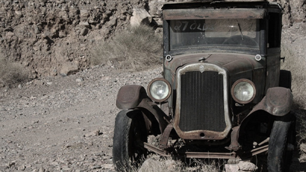 A vintage car abandoned in the desert.